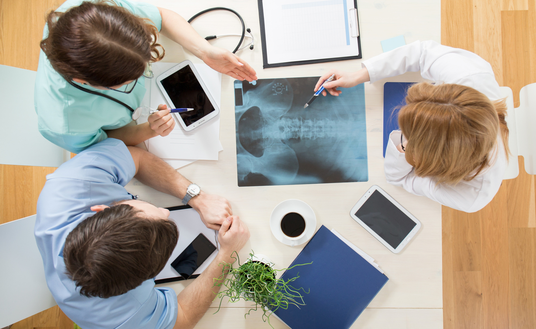 Three young physicians looking at xray of spinal column